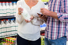 Smiling couple buying milk and checking list Stock Image