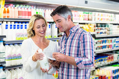Smiling couple buying milk and checking list Royalty Free Stock Image