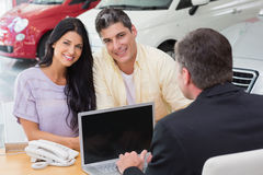 Smiling couple buying a new car Stock Images