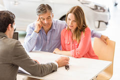 Smiling couple buying a new car Stock Image