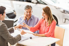 Smiling couple buying a new car. At new car showroom Stock Photos