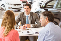 Smiling couple buying a new car. At new car showroom Royalty Free Stock Photos