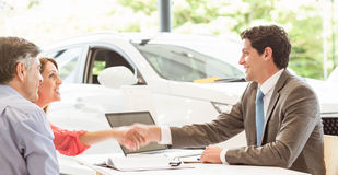 Smiling couple buying a new car Stock Photography