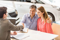 Smiling couple buying a new car Stock Photo