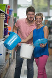 Smiling Couple Buying Trash Can In Supermarket Stock Photo