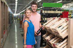 Smiling Couple Buying Vino In Supermarket. Beautiful Young Couple Shopping For Vino In Produce Department Of A Grocery Store - Supermarket - Shallow Deep Of Royalty Free Stock Photo