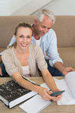 Smiling couple calculating their bills at the couch Royalty Free Stock Image