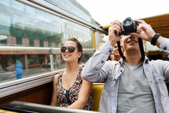 Smiling couple with camera traveling by tour bus Stock Image