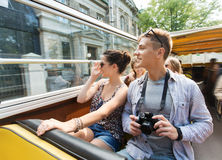 Smiling couple with camera traveling by tour bus. Travel, tourism, summer vacation, sightseeing and people concept - smiling teenage couple with camera traveling royalty free stock photos