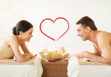 Smiling couple with candles and drinks in spa royalty free stock photo