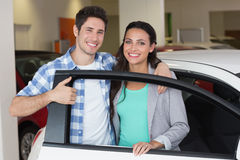 Smiling couple in a car shop Royalty Free Stock Photos