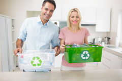 Smiling couple carrying recycling containers in kitchen Royalty Free Stock Images