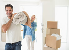 Smiling couple carrying rolled rug after moving in house Royalty Free Stock Photo