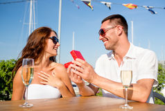 Smiling couple with champagne and gift at cafe Royalty Free Stock Photo