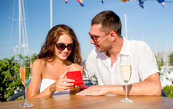 Smiling couple with champagne and gift at cafe Royalty Free Stock Images
