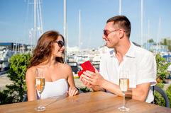 Smiling couple with champagne and gift at cafe Stock Images