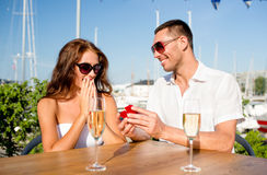 Smiling couple with champagne and gift at cafe Royalty Free Stock Photography