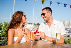 Smiling couple with champagne and gift at cafe Royalty Free Stock Image