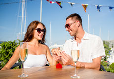 Smiling couple with champagne and gift at cafe Royalty Free Stock Photos