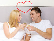 Smiling couple with champagne glasses in bed Stock Images