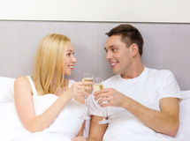 Smiling couple with champagne glasses in bed Stock Photography