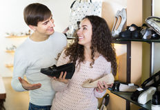 Smiling couple chooses summer female shoes Stock Photo