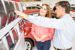 Smiling couple choosing the color of their new car Royalty Free Stock Image