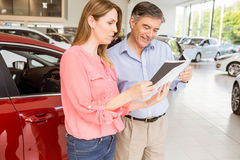 Smiling couple choosing the color of their new car Stock Photography