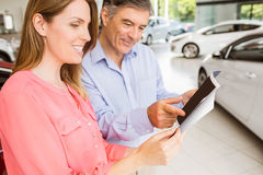 Smiling couple choosing the color of their new car Royalty Free Stock Photos