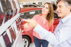 Smiling couple choosing the color of their new car Stock Image