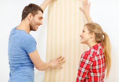 Smiling couple choosing wallpaper for new home Royalty Free Stock Photos