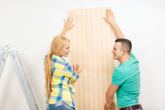 Smiling couple choosing wallpaper for new home Royalty Free Stock Image