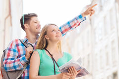 Smiling couple with city guide and backpack Stock Photo