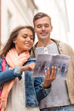 Smiling couple with city guide exploring town Stock Photography