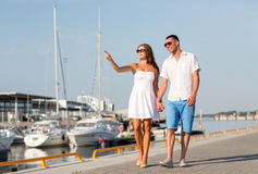 Smiling couple in city. Love, travel, tourism and people concept - smiling couple wearing sunglasses walking at harbor and pointing finger royalty free stock photography