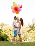 Smiling couple in city. Love, wedding, summer, dating and people concept - smiling couple wearing sunglasses with balloons hugging in park Stock Photography