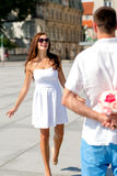 Smiling couple in city. Love, wedding, summer, dating and people concept - smiling couple wearing sunglasses with bunch of flowers looking at each other in city Royalty Free Stock Photography