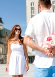 Smiling couple in city. Love, wedding, summer, dating and people concept - smiling couple wearing sunglasses with bunch of flowers looking at each other in city Stock Photo