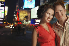 Smiling Couple On City Street At Night. Closeup portrait of a smiling young couple on city street at night Royalty Free Stock Photography