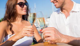 Smiling couple clinking champagne glasses at cafe Royalty Free Stock Photography