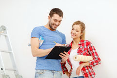 Smiling couple with clipboard and wallpaper roll Stock Photo
