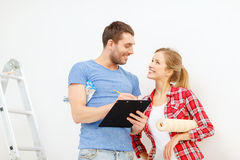 Smiling couple with clipboard and wallpaper roll Stock Images