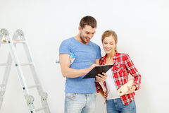Smiling couple with clipboard and wallpaper roll Stock Photography