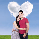 Smiling couple with clouds shaped of heart Stock Image