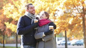 Smiling couple with coffee cups in autumn park stock video footage