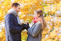 Smiling couple with coffee cups in autumn park Royalty Free Stock Photo