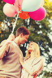 Smiling couple with colorful balloons in park Royalty Free Stock Photography