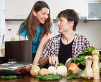 Smiling couple cooking with notebook Stock Photography