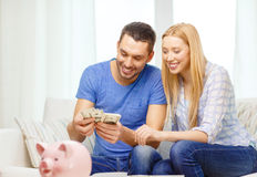Smiling couple counting money at home Stock Photography