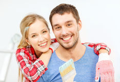 Smiling couple covered with paint with paint brush Stock Photos